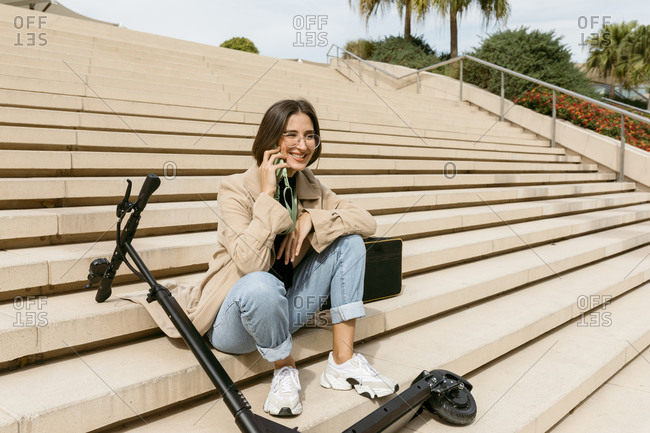 Smiling woman talking through mobile phone while sitting by electric push scooter on staircase