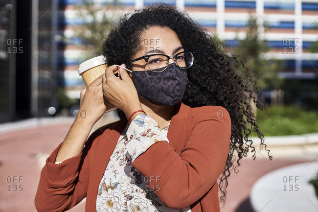 Woman wearing protective face mask while holding reusable bamboo cup in city during sunny day