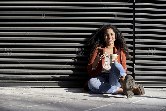 Smiling woman holding reusable cup and smart phone while sitting against black shutter