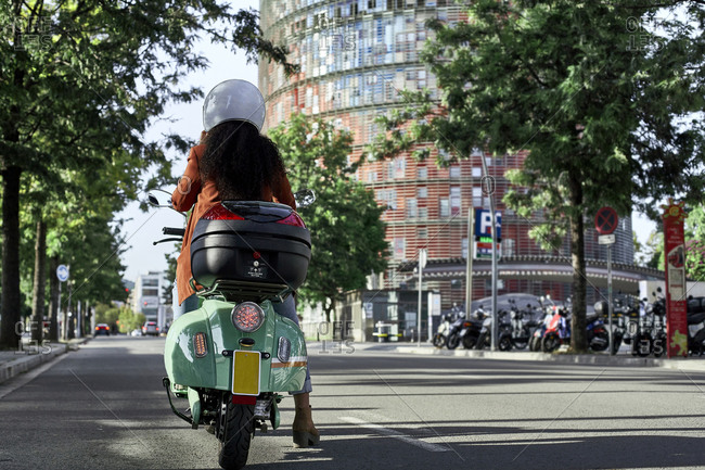 Young woman riding motor scooter in city on sunny day