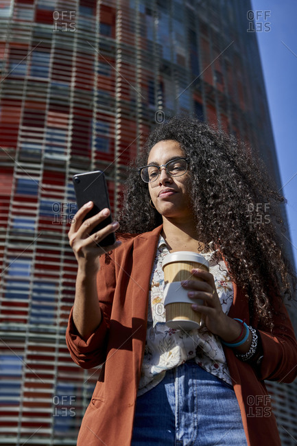 Woman using smart phone holding bamboo cup while standing against building in city