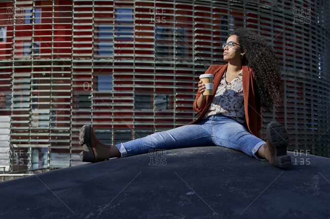 Young woman holding bamboo mug looking away sitting on footpath against building