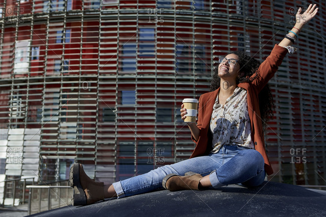 Cheerful woman with hand raised holding bamboo mug while sitting on floor against office building