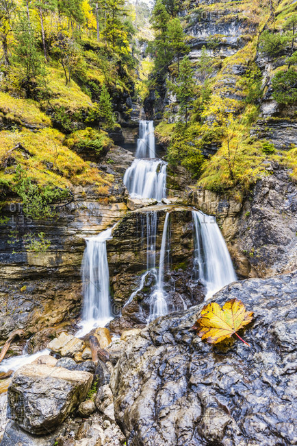 Waterfall and creek in autumn landscape