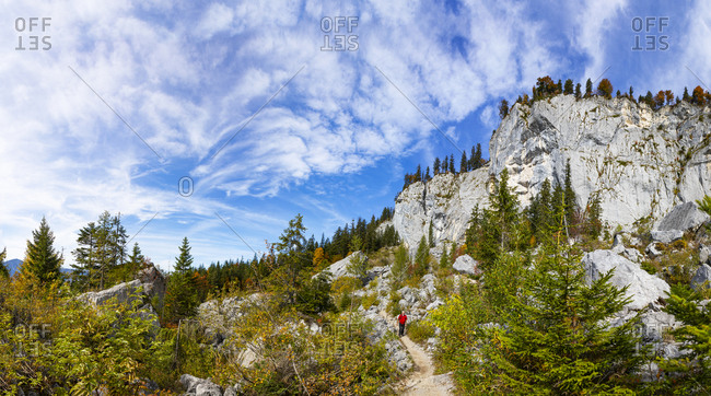 Senior man hiking on mountain against sky at Salzkammergut- Austria