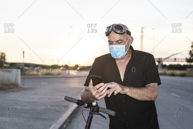 Attractive 60-year-old mature man on electric scooter with face mask texting message