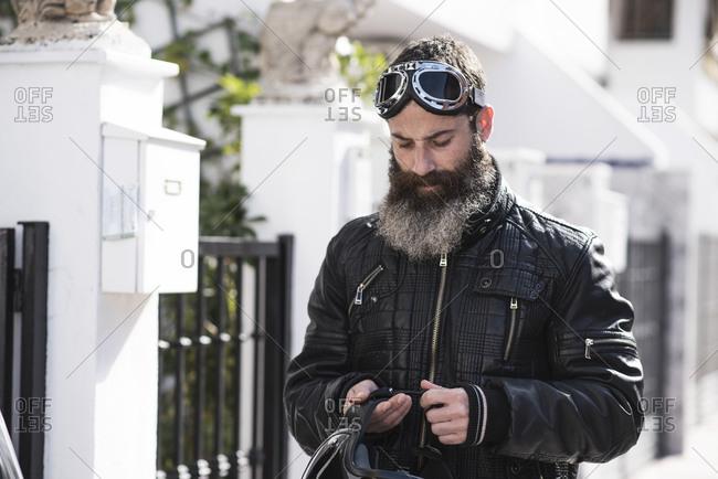Biker bearded man adjusting helmet before travel on his motorbike