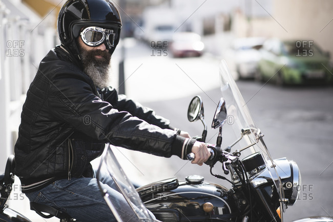 Bearded man prepares to go out with his sidecar motorcycle peeking out of the garage of his house
