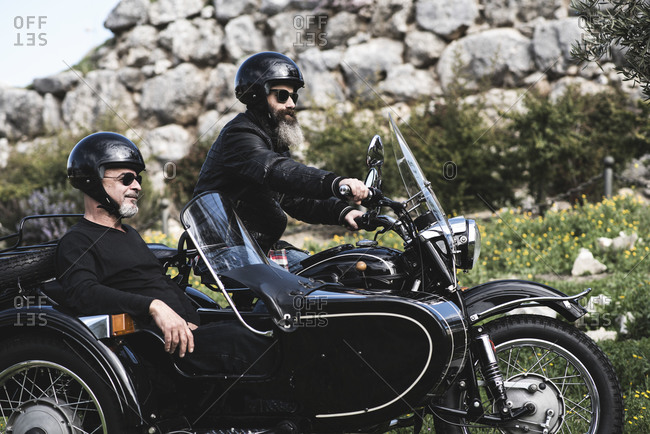Two men in a sidecar stop to contemplate the landscape during a trip