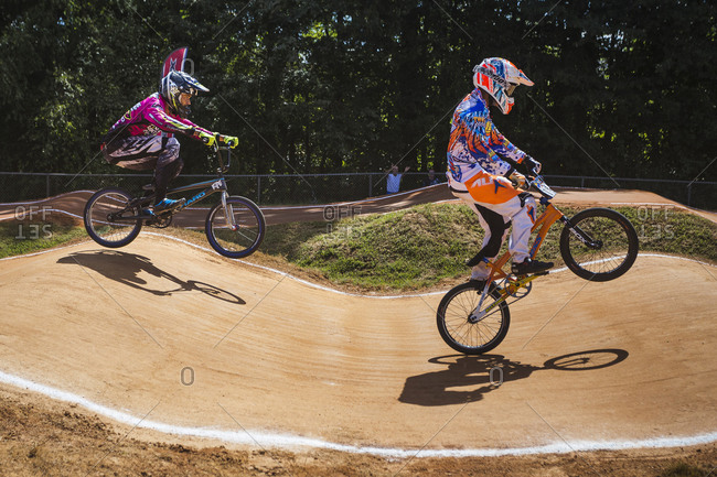 Raleigh, North Carolina - September 19, 2015: Two racers riding over hill while competing in the 2015 Tar Heel National BMX Regional Championship race, one popping a wheelie