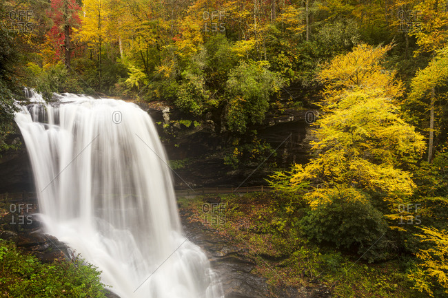 Beautiful fall colors surround Dry Falls outside of Highlands, North Carolina within the Nantahala National Forest