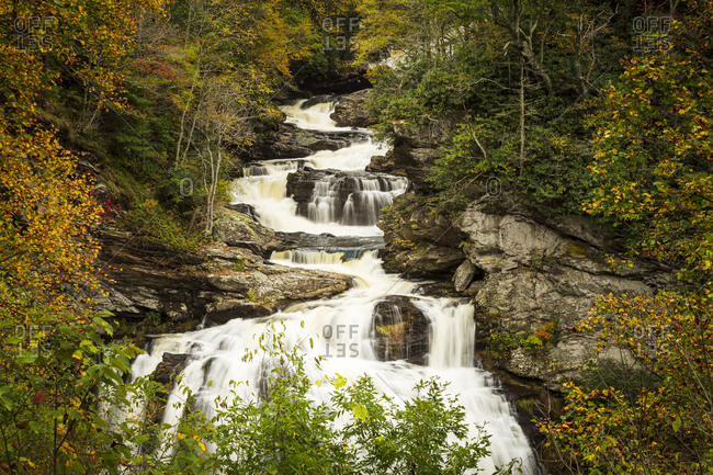 Fall foliage surrounding cascading river of Cullasaja Falls outside of Highlands, North Carolina
