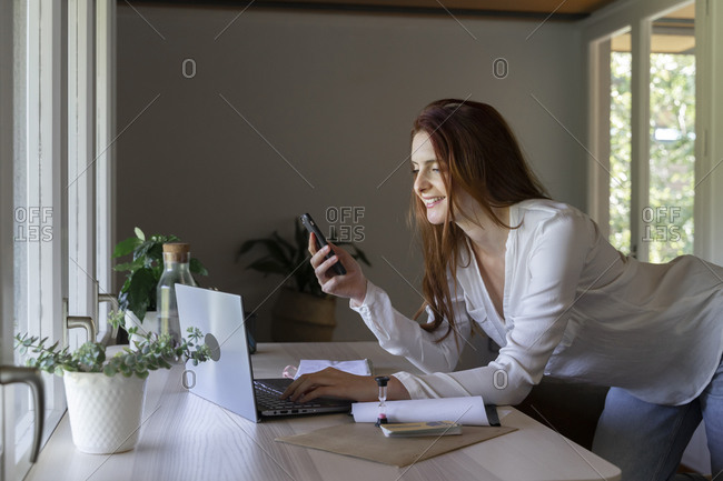 Smiling psychologist using mobile phone while working on laptop at home