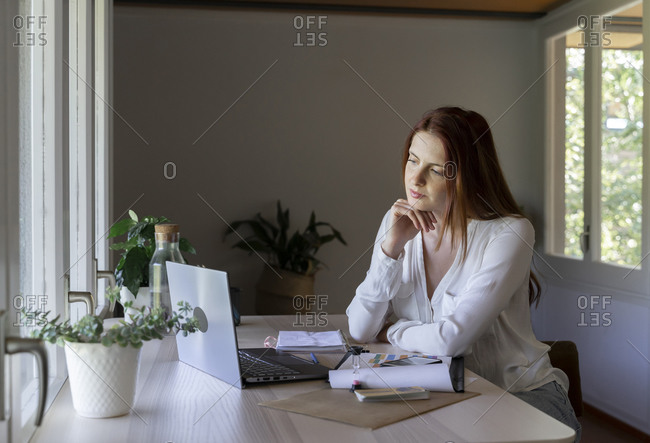 Thoughtful psychologist looking at laptop while sitting with hand on chin at home