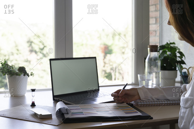 Doctor writing in book while working on laptop at home