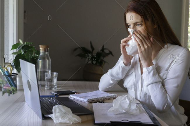 Sick woman talking to doctor on laptop at home- cleaning nose with tissue paper