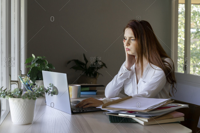 Tired psychologist working on laptop while sitting at home