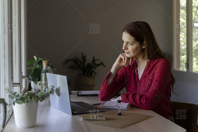 Psychologist with head in hands listening to video call on laptop while sitting at home