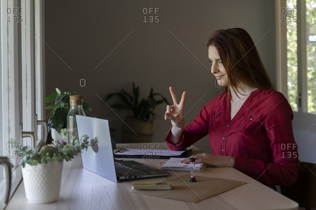 Doctor showing peace sign to video call on laptop while sitting at home