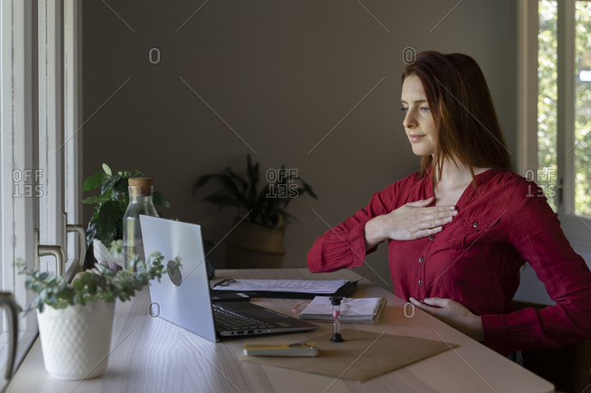 Doctor showing breathing therapy on video call through laptop while sitting at home