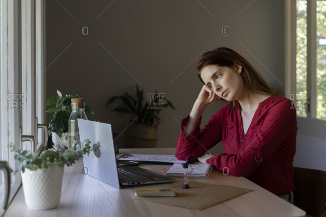 Doctor with head in hands listening to video call on laptop while sitting at home