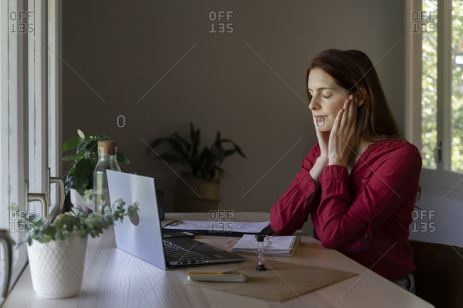 Young psychologist showing listening therapy on video call while sitting at home