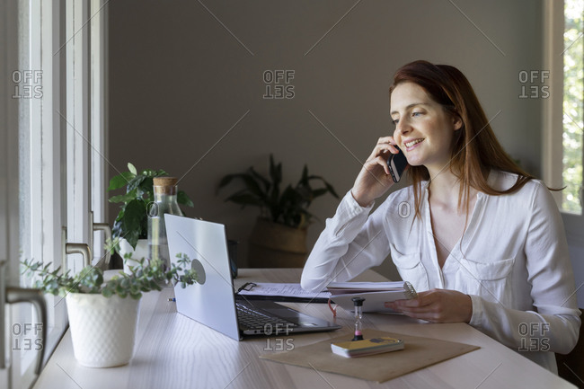 Smiling doctor talking on mobile phone while working on laptop at home