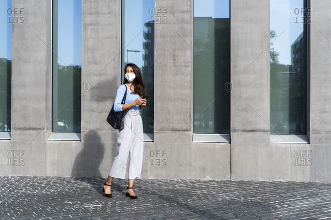 Businesswoman in face mask standing on footpath by building during coronavirus crisis