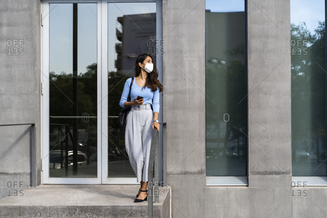 Young woman wearing protective face mask standing at entrance of building during COVID-19
