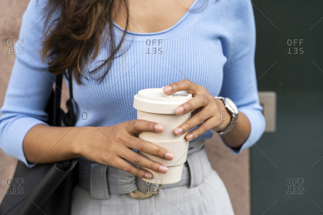 Young woman holding disposable coffee cup