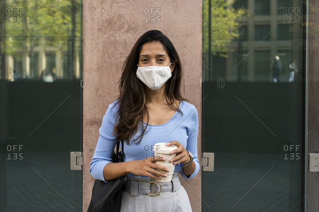 Young businesswoman in protective face mask holding disposable coffee cup while standing against building