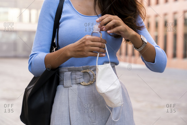 Businesswoman holding hand sanitizer and protective face mask while standing on footpath