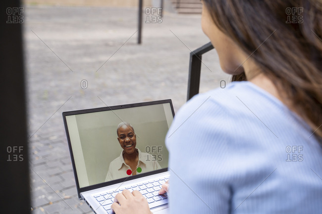 Businesswoman video calling through laptop while sitting outdoors