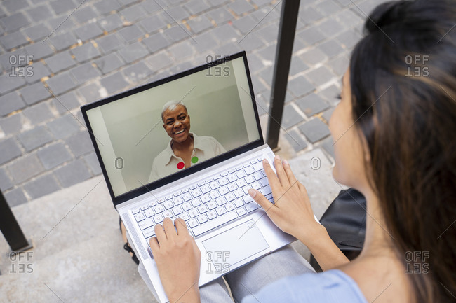 Businesswoman video calling through laptop while sitting on steps