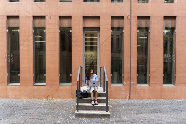 Businesswoman using laptop while sitting on steps at entrance of office building