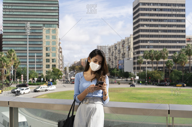 Businesswoman in protective face mask using smart phone while leaning on railing during coronavirus outbreak