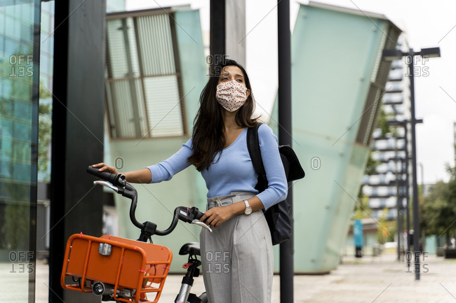 Beautiful woman wearing protective face mask while walking with bicycle in city during COVID-19