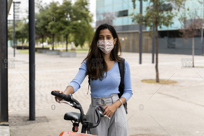 Beautiful woman wearing protective face mask while standing with bicycle in city during COVID-19 pandemic