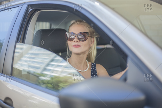 Young woman wearing sunglasses driving car in city