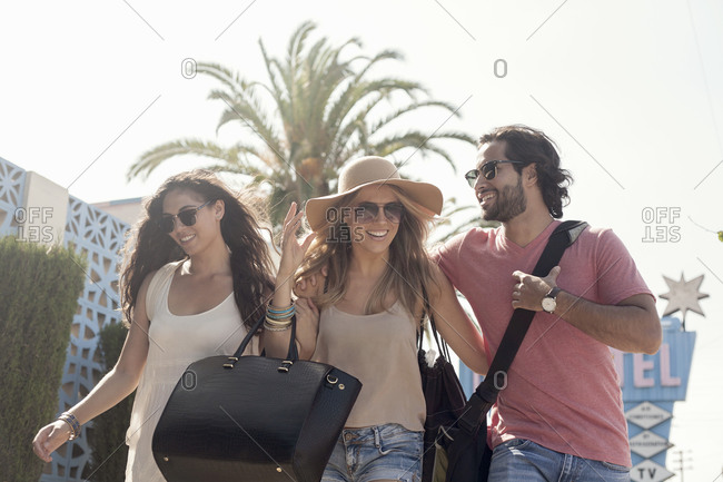 Smiling male and female friends in sunglasses walking against sky during sunny day