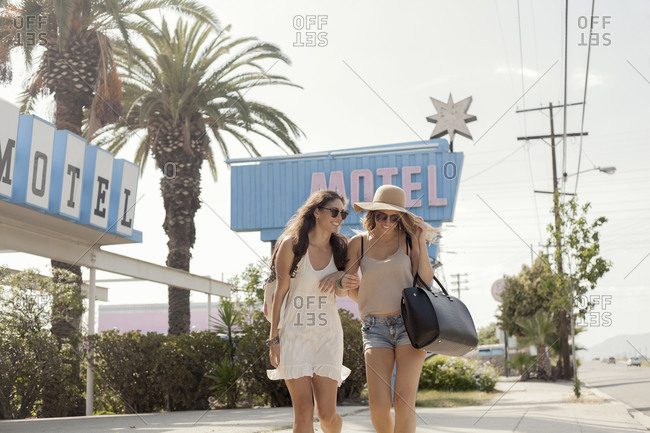 Smiling female friends in sunglasses walking on sidewalk during sunny day