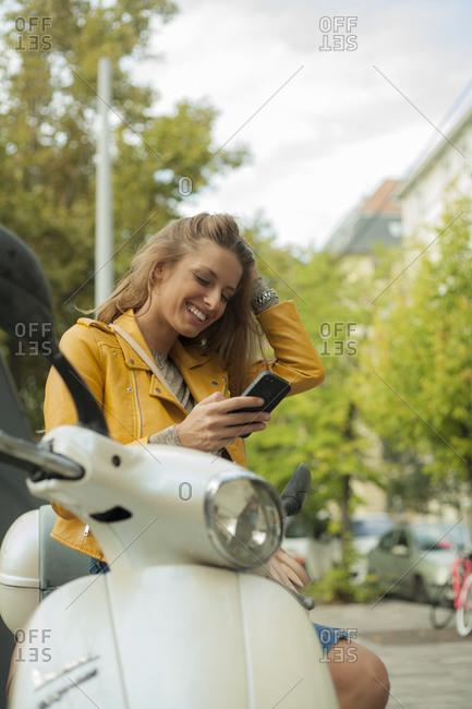 Smiling woman checking smart phone while sitting on motorbike