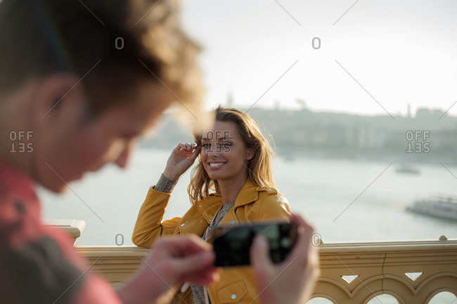 Young man taking photograph of young woman with smart phone on bridge against sky