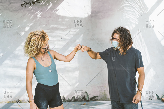 Couple with face mask giving fist bump while standing against wall