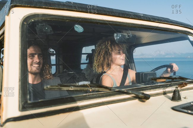 Smiling woman driving while sitting by man in car at beach