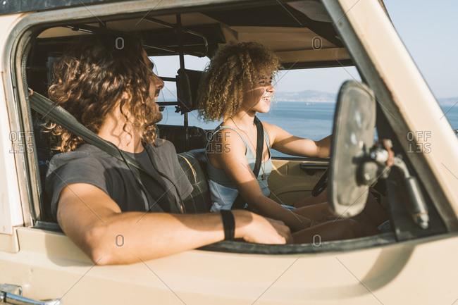 Man looking at woman driving car at beach