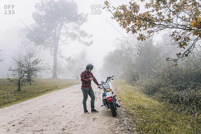 Man using smart phone while standing by motorcycle on dirt road