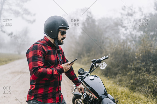 Male biker talking on speaker of smart phone while standing by motorcycle in foggy weather