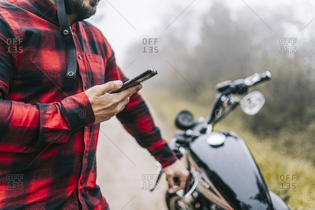Male biker using smart phone while standing by motorcycle during road trip