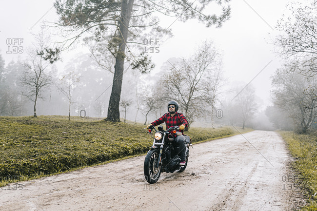 Male biker riding motorcycle on dirt road in foggy weather